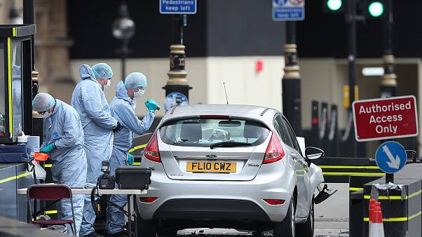 Image: Police forensics officers work around a silver Ford Fiesta car that