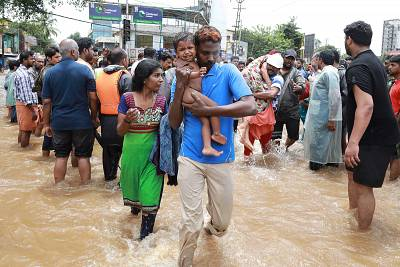 Volunteers and rescue personal evacuate local residents in a residential area of the Indian state of Kerala on Friday.