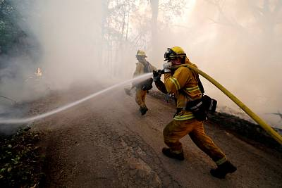 A firefighter knocks down hotspots to slow the spread of the River Fire (Mendocino Complex) in Lakeport, California, on July 31, 2018.
