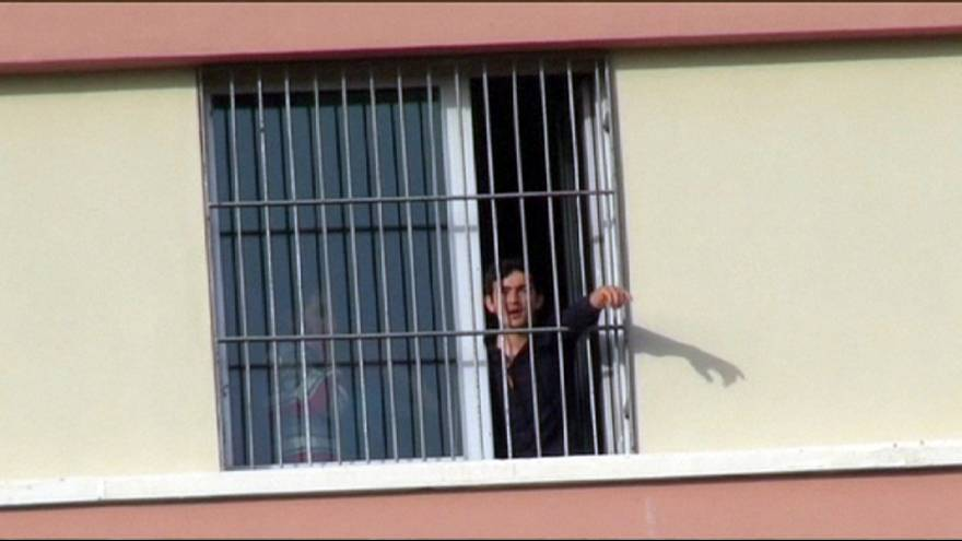 Deported migrants call for freedom from behind barred windows