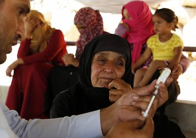 Palestinian refugees and Bedouins receive medical check ups from the UNRWA\' mobile team on the outskirts of of Hebron, in the West Bank, on August 9, 2018.