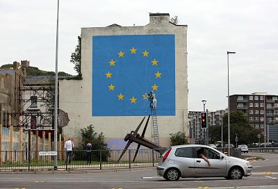 A large, colorful reminder of the looming upheaval visible to drivers approaching Dover's sprawling harbor. A blue and yellow Banksy mural, depicting the removal of one star from the E.U. flag, covers the entire end of a roadside building and has become a tourist attraction in its own right.