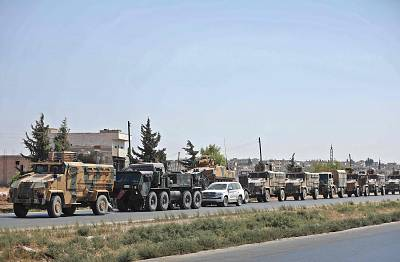 A convoy of Turkish military vehicles travels on a highway near the town of Saraqib in Syria\'s northern Idlib province on Wedneday.