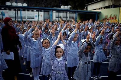Palestinian schoolgirls participate in the morning exercise at an UNRWA-run school, on the first day of a new school year, in Gaza City on August 29, 2018.