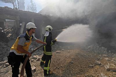 Firefighters battle a blaze after an airstrike in Jadraya, Syria, on Tuesday.