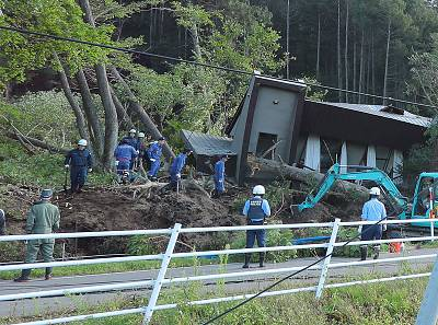 Police officers and fire fighters search for missing persons at a collapsed house following a large landslide that occurred after an earthquake hit Hokkaido, in Atsuma, northern Japan, on September 6, 2018.