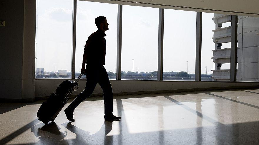 Image: A traveler passes through Philadelphia International Airport Thursda