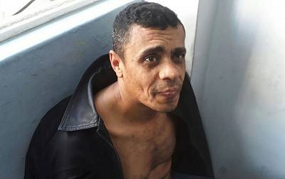 """In this photo released by the Military Police, Adelio Bispo de Oliveira, suspected of stabbing Jair Bolsonaro, a leading Brazilian presidential candidate, sits after being detained in Juiz de Fora, Brazil, on Sept. 6, 2018. Officials and Bolsonaro\'s son said the far-right candidate was in stable condition, though the son also said Bolsonaro suffered severe blood loss and arrived to the hospital """"almost dead."""""""