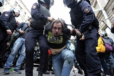 Police officers detain a demonstrator during a rally protesting a rise in the retirement age in St. Petersburg, Russia, on Sunday.