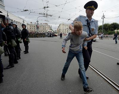 A youth is escorted away from a protest in St. Petersburg, Russia, on Sunday.