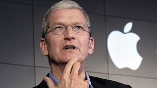 Image: Apple CEO Tim Cook responds to a question during a news conference