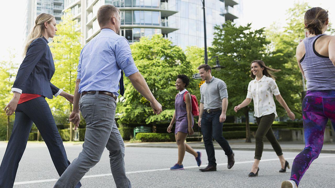 People cross a busy street