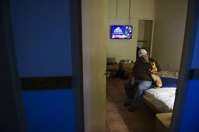 55-year-old retiree Ivan Ferreira sits on the edge of his bed in a hotel room with his dog Ovito where he has taken refuge for months after Hurricane Maria damaged his home, in Cabo Rojo, Puerto Rico.