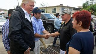 Image: U.S. President Donald Trump chats with residents in a storm damaged