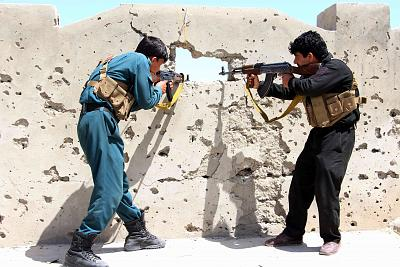 Members of the Afghan security forces fire at Taliban fighters in Nad Ali district of Helmand province in April 2017.