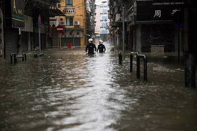 Rescue workers make their way through flood waters after Typhoon Mangkhut hit Macau on Sunday.