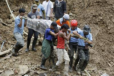 Rescuers carry the body uncovered after the landslide in Itogon.
