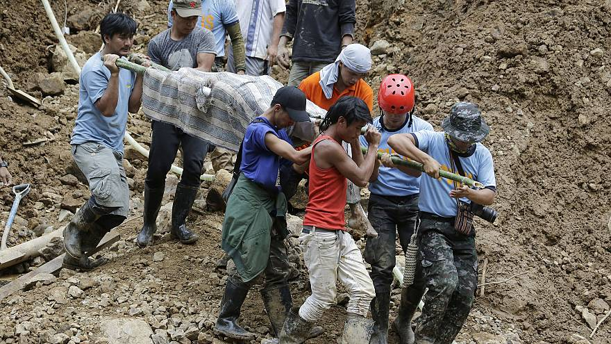 Image: Rescuers carry a body from the site where victims are believed to ha