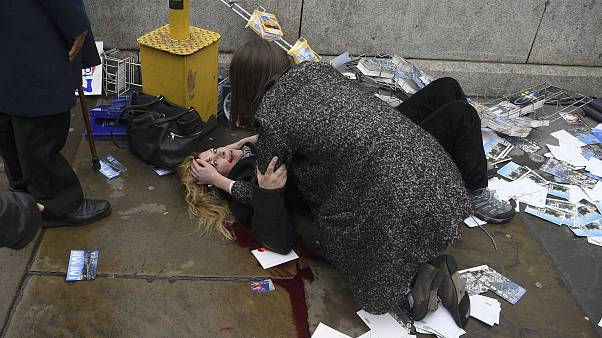 Image: A woman lies injured after a shotting incident on Westminster Bridge