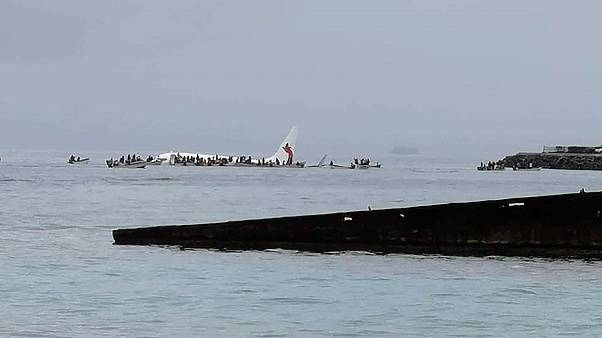 Image: People are evacuated from an Air Niugini plane which crashed in the