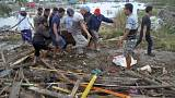 Image: Residents carry a bag containing the body of a tsunami victim in Pal