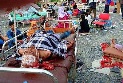 Survivors rest on trollies outside a hospital in Palu, Indonesia.
