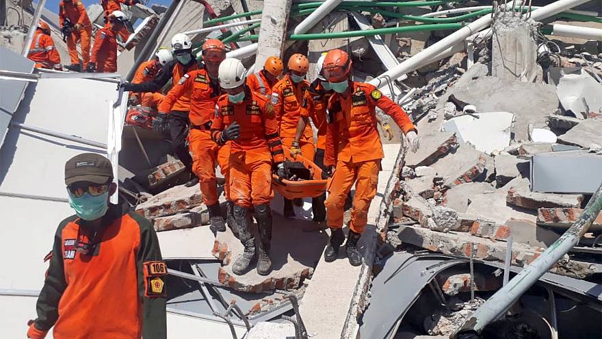 Image: A search and rescue team evacuates a victim from the ruins of the Ro