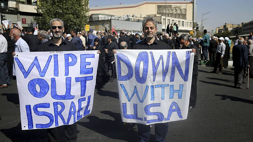 Image: Men hold up anti-American and anti-Israeli placards at a rally conde