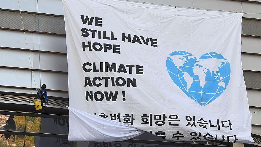 "Image: Greenpeace activists display a big banner reading ""We still have hop"
