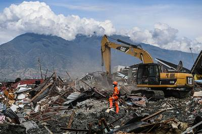 A search and rescue team uses heavy equipment to recover bodies from the debris in Petobo on Oct. 8.