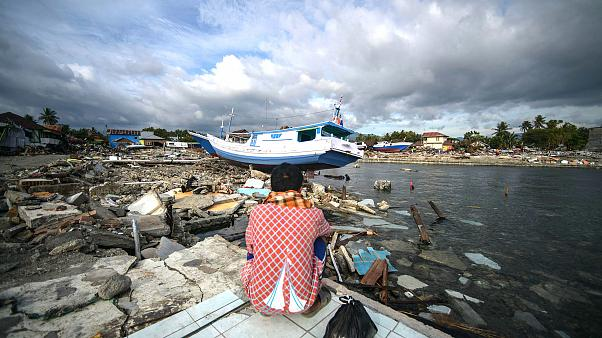 Image: A resident looks at a washed out boat in Wani