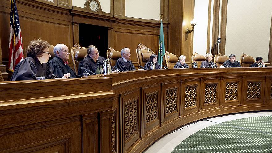 Justices on the Washington state Supreme Court listen during a hearing in O