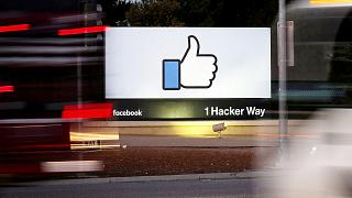Image: The entrance sign to Facebook headquarters is seen through two movin