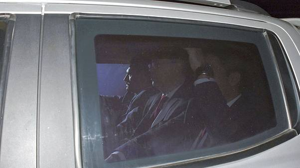 Image: Andrew Brunson, center, sits inside a car as he arrives for his tria