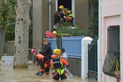 Firefighters help children evacuate a flooded street following heavy rains that saw rivers bursting banks on Oct. 15, 2018 in Trebes, near Carcassone, southern France.