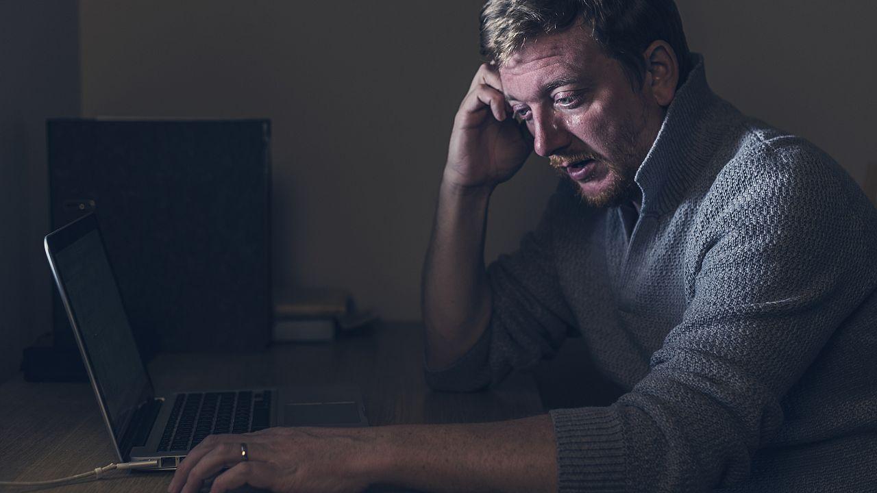 Image: Sad Man at Home Desk
