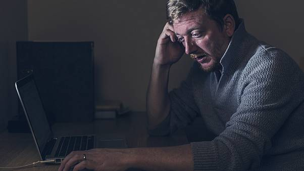 Image: Sad Man at Home Desk