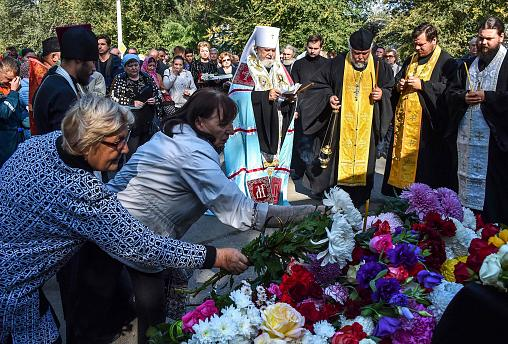 Image: People lay flowers for the victims during a church service in Kerch,