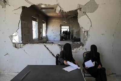 Women wait to be examined at a damaged hospital in Douma, Syria, on Sept. 17.