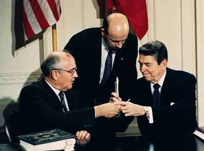 President Ronald Reagan, right, and Soviet leader Mikhail Gorbachev exchange pens during the Intermediate Range Nuclear Forces Treaty signing ceremony on Dec. 8, 1987. Gorbachev\'s translator Pavel Palazhchenko stands in between the men.