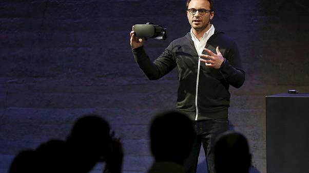 Oculus CEO Brendan Iribe displays a virtual reality headset during an event