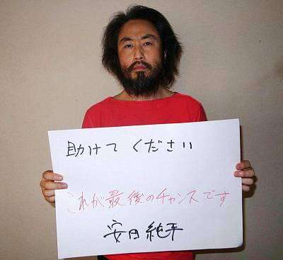 "Japanese freelance journalist Jumpei Yasuda in May 2016, holding a handwritten sign in Japanese that reads: ""Please help. This is the last chance."""