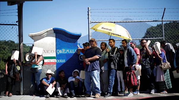 Image: Central American migrants queue at a border connecting Guatemala and