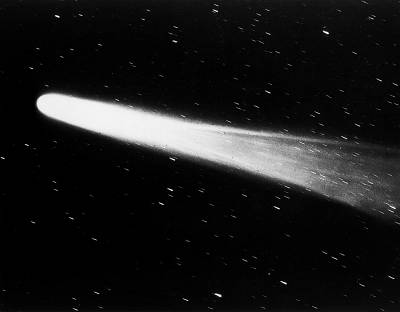Close view of Halley\'s comet streaking past stars in the night sky.