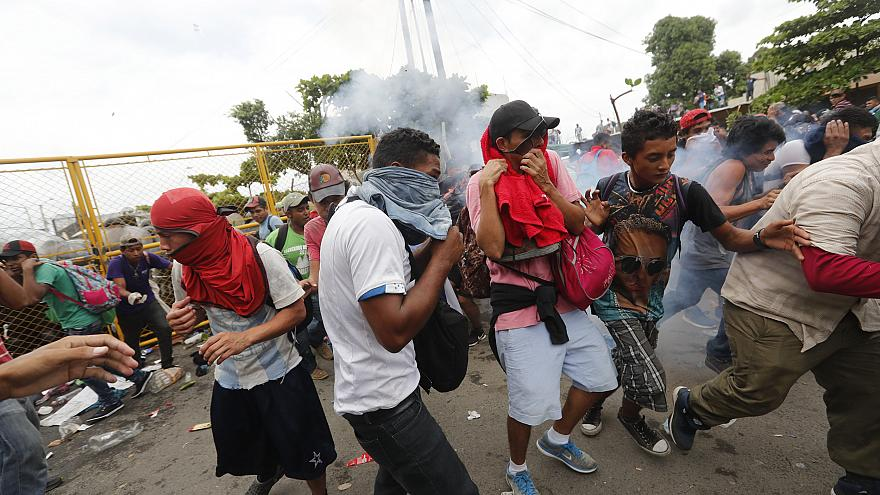 Image: Migrants break the fence between Guatemala and Mexico and fight poli