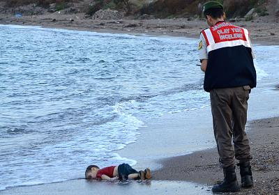 A police officer stands next to the body of Aylan Kurdi, a Syrian toddler who drowned and washed ashore in Turkey in 2015.