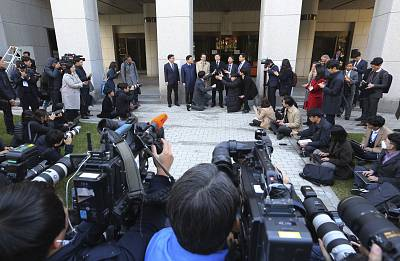 Oh Seung-hun, top center, speaks to the media in Seoul, South Korea, after Thursday\'s verdict.