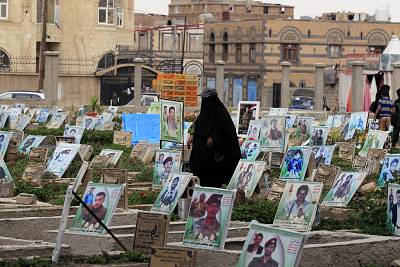 A woman walks among graves with portraits of Houthi militia members at a cemetery in Sanaa, Yemen.