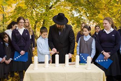"Rabbi Yehuda Teichtal lights candles with students during an event to mark the 80th anniversary of Kristallnacht, the ""Night of Broken Glass,"" at the Jewish Traditional School in Berlin on Nov. 7, 2018."