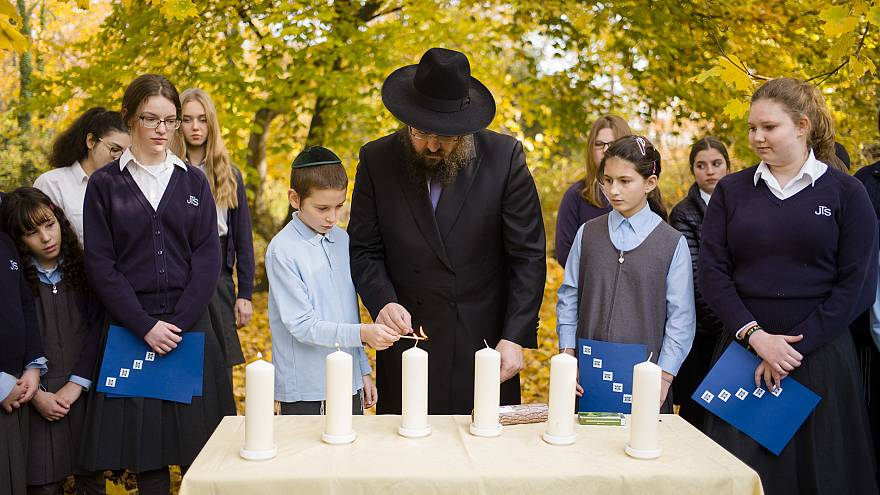 Rabbi Yehuda Teichtal lights candles with students during an event to mark